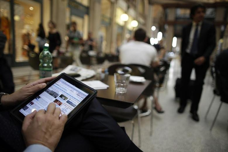 A man poses with his iPad tablet as he sits in a bar, in this photo illustration taken in Rome September 20, 2012. REUTERS/Tony Gentile