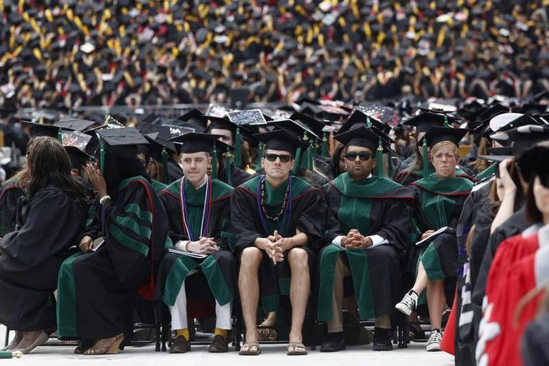 A student in flip flops and shorts (C) watches as U.S. President Barack Obama (not pictured) receives an honorary degree during the spring commencement ceremony at Ohio State University in Columbus, May 5, 2013. REUTERS/Jason Reed