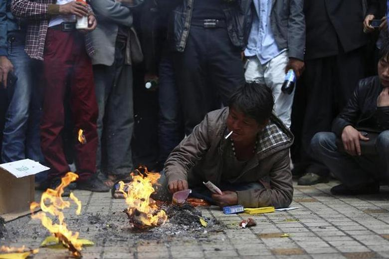 A man, whose relative was killed in a knife attack, lies on the floor as he burns offerings at Kunming railway station in Kunming, Yunnan province March 3, 2014. REUTERS/Wong Campion