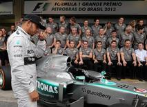 Mercedes Formula One drivers Lewis Hamilton of Britain arrive to pose with team members at the Interlagos circuit in Sao Paulo November 24, 2013. REUTERS/Paulo Whitaker