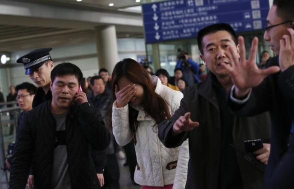 A woman (C), believed to be the relative of a passenger onboard Malaysia Airlines flight MH370, covers her face as she cries at the Beijing Capital International Airport in Beijing March 8, 2014. REUTERS-Kim Kyung-Hoon