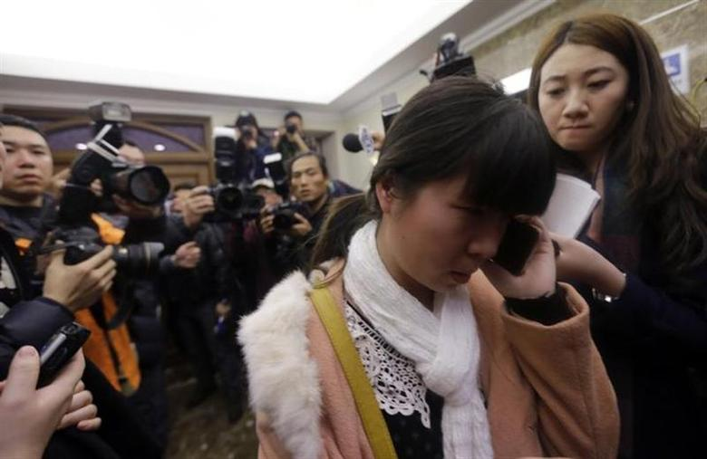 A relative of a passenger of Malaysia Airlines flight MH370 talks on a mobile phone as journalists attempt to interview her at a hotel in Beijing March 8, 2014. . REUTERS/Jason Lee