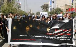 "Iraqi Protesters hold a banner during a demonstration against the draft of the ""Al-Jafaari"" Personal Status Law during International Women's Day in Baghdad March 8, 2014. REUTERS/Thaier al-Sudani"