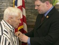 "World War II veteran Richard ""Dick"" Faulkner (L), is presented the Purple Heart by U.S. Representative Dan Maffei during a ceremony in Auburn, New York March 8, 2014. REUTERS/Mike Bradley"