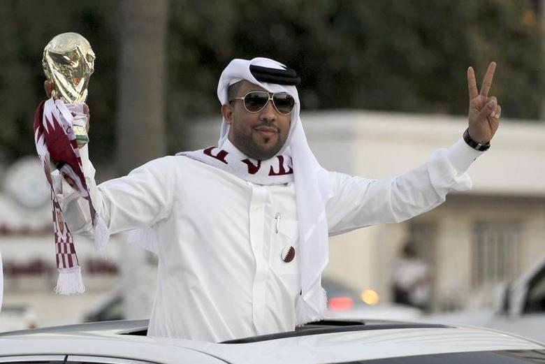A Qatari fan holds a replica of the World Cup trophy as he celebrates in Doha December 3, 2010. REUTERS/Fadi Al-Assaad