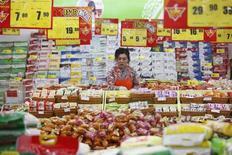 Una empleada arregla las etiquetas de precios de los productos en un supermercado de la ciudad china de Huabei. Marzo 9, 2014. REUTERS/Stringer.