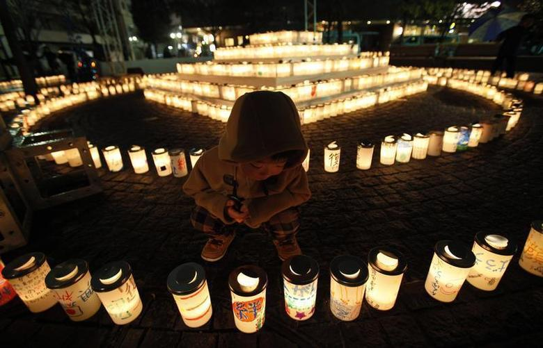 A boy looks at a candle light with a character reading: ''bond'', written on the candle holder at a memorial held in remembrance of victims of the March 11, 2011 earthquake and tsunami in Koriyama, Fukushima prefecture March 11, 2012. REUTERS/Yuriko Nakao