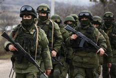 Вооруженные люди, предположительно, российские военные, маршируют недалеко от украинской военной части под Симферополем в Крыму 9 марта 2014 года. REUTERS/Thomas Peter