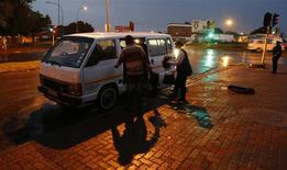 Passengers board Zakes Hadebe's minibus taxi early in the morning in Soweto February 21, 2014.REUTERS/MIke Hutchings