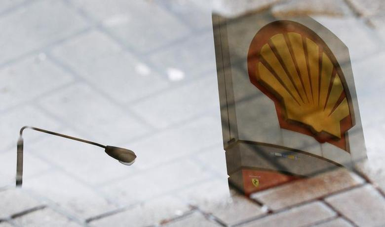 A Shell petrol station sign is seen reflected in a puddle in London February 4, 2010. REUTERS/Luke Macgregor