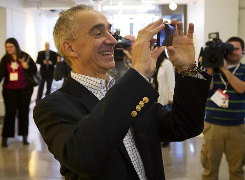 Google Senior Vice President and Chief Financial Officer Patrick Pichette takes a picture with his phone at the new Google office in Toronto, November 13, 2012. REUTERS/Mark Blinch/Files