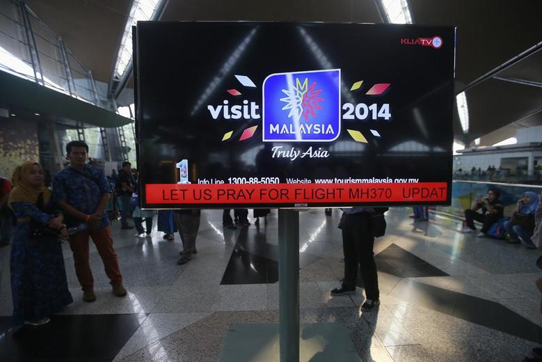 An information screen displays a message ''Let Us Pray For Flight MH370'', regarding the missing Malaysia Airlines flight, at Kuala Lumpur International Airport in Sepang March 8, 2014. REUTERS/Samsul Said