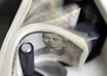 Банкноты в 10000 японских иен в аппарате для подсчета денег в отделении World Currency Shop в Токио 9 августа 2010 года. Курс иены малоподвижен после сохранения стимулов и ухудшения прогнозов Банка Японии. REUTERS/Kim Kyung-Hoon