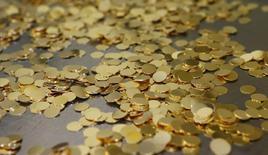 Заготовки для золотых монет на монетном дворе в Вене 23 апреля 2013 года. Цены на золото растут на фоне опасений за экономический рост Китая и геополитического кризиса на Украине. REUTERS/Leonhard Foeger