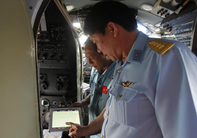 Senior Colonel Do Duc Minh (R), deputy chief of staff of the Vietnam Air Force, talks with Captain Vu Duc Long, while pointing at a map detailing the flight path that Captain Vu and his AN-26 crew will be taking for their search and rescue mission of the missing Malaysia Airlines flight MH370, before departing for their mission at a military airport in Ho Chi Minh city March 11, 2014.REUTERS/Kham