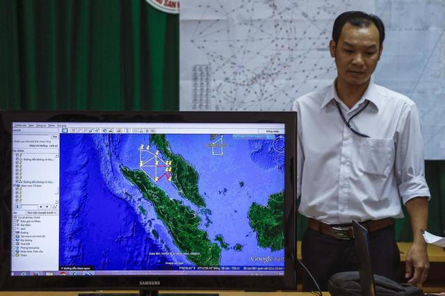 A Vietnamese officer stands next to a TV screen showing a flight route during a news conference about their mission to find missing Malaysia Airlines flight MH370 at Phu Quoc Airport in Phu Quoc Island, March 11, 2014. REUTERS/Athit Perawongmetha