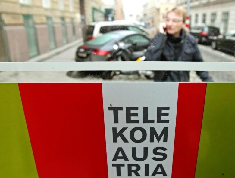 A man talks on his mobile phone outside a Telekom Austria phone booth in Vienna January 9, 2014. REUTERS/Heinz-Peter Bader