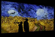 """The shadow of a journalist is cast on the projection of the painting """"Champ de Ble aux Corbeaux"""", Auvers sur Oise in July 1890, by painter Vincent van Gogh during press day for the exhibition, """"Van Gogh/Artaud The Man Suicided by Society"""", at the Musee d'Orsay in Paris March 10, 2014. REUTERS/John Schults"""