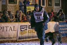 Dallas Seavey runs with his lead dog after greeting the crowd gathered at the finish line at 4am after winning the Iditarod dog sled race in Nome, Alaska, March 11, 2014. REUTERS/Nathaniel Wilder