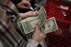 Un cliente cuenta dólares en una tienda de la cadena minorista Target en Torrington, EEUU, nov 25 2011. El euro se depreciaba frente al dólar y al yen el martes después de que funcionarios del Banco Central Europeo indicaron que los operadores podrían haber pasado por alto el mensaje de que el banco aún podría actuar para estimular a la economía. REUTERS/Jessica Rinaldi