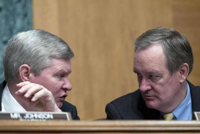 U.S. Senator Tim Johnson (L) (D-SD) speaks with U.S. Senator Mike Crapo (R-ID), as SEC Chair Mary Jo White (not pictured) and Commodity Futures Trading Commission Chair Gary Gensler (not pictured) testify, at a Senate Banking, Housing and Urban Affairs Committee hearing on Capitol Hill July 30, 2013. REUTERS/Jose Luis Magana