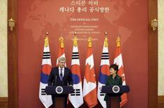 Canadian Prime Minister Stephen Harper (L) answers questions from reporters as South Korean President Park Geun-hye listens during a joint news conference after their meeting at the presidential Blue House in Seoul, March 11, 2014. REUTERS/Lee Jin-man/Pool