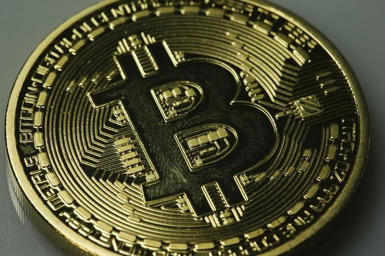 A mock Bitcoin is displayed on a table in an illustration picture taken in Berlin January 7, 2014. REUTERS/Pawel Kopczynski/Files