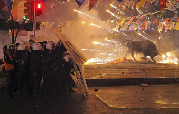 Riot policemen shield themselves as fireworks thrown by protesters explode next to the statue of a bull, during an anti-government protest in the Kadikoy district of Istanbul March 11, 2014. REUTERS-Stringer