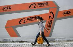 A woman walks past an Alibaba advertisement on a wall in Hangzhou, Zhejiang province September 26, 2013. REUTERS/Chance Chan