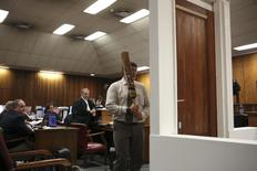 A policeman demonstrates the effect of hitting of a bathroom door with a cricket bat during the trial of South African Paralympic athlete Oscar Pistorius in the North Gauteng High Court in Pretoria, March 12, 2014. Pistorius is on trial for murdering his girlfriend Reeva Steenkamp at his suburban Pretoria home on Valentine's Day last year. REUTERS/Alexander Joe/Pool