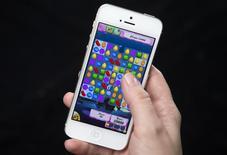 Una mujer muestra el juego Candy Crush instalado en un teléfono iPhone de Apple en Nueva York, feb 18 2014. King Digital Entertainment, la compañía que creó el célebre juego para dispositivos móviles Candy Crush Saga, prevé una valoración de hasta 7.600 millones de dólares cuando salga a la bolsa este mes aprovechando el fuerte interés por invertir en el sector de tecnología. REUTERS/Carlo Allegri