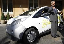 Vincent Bollore, CEO of investment group Bollore, poses by an electric car following a news conference in London March 12, 2014. REUTERS/Olivia Harris