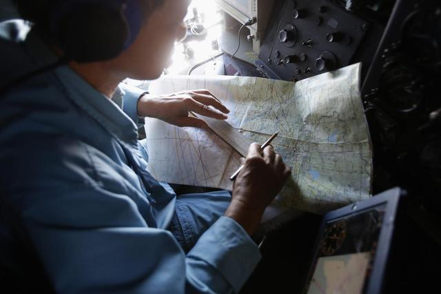 A military officer works on a map onboard a Vietnam Air Force AN-26 aircraft during a mission to find the missing Malaysia Airlines flight MH370, off Con Dao island, March 13, 2014.REUTERS/Kham