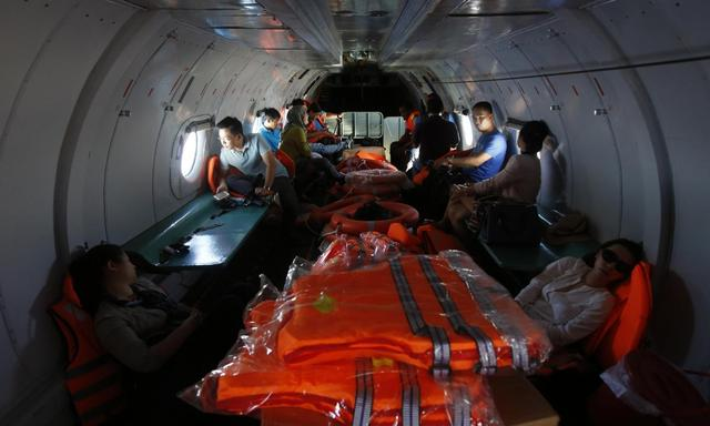Malaysian and Chinese journalists look for the missing Malaysia Airlines flight MH370, during a mission on a Vietnam Air Force AN-26 aircraft, off Con Dao island March 13, 2014. REUTERS/Kham