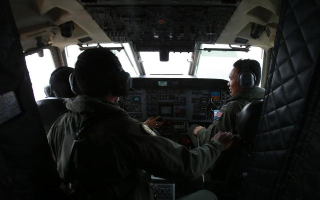 Royal Malaysian Air Force pilots work in the cockpit of a Malaysian Air Force CN235 aircraft during a Search and Rescue (SAR) operation to find the missing Malaysia Airlines flight MH370, in the Straits of Malacca March 13, 2014. REUTERS/Samsul Said