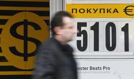 Иужчина проходит мимо пункта обмена валюты в Москве 3 марта 2014 года. Рубль торгуется с минимальными изменениями на границе валютного коридора, где Центробанк за счет своих резервов и в отсутствие других продавцов валюты покрывает спрос на безопасные активы - участники рынка выкупают валюту у регулятора, опасаясь негативного эффекта от возможных западных санкций против РФ и неопределенной ситуации вокруг Украины и будущего крымской автономии. REUTERS/Maxim Shemetov