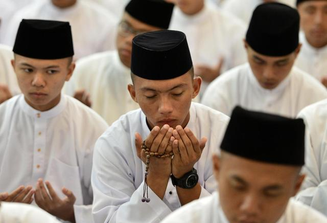 Bruneian Muslims pray during mass prayers for the passengers of Malaysian Airlines flight MH370 at Jame'asr Hassanil Bolkiah Mosque in Bandar Seri Begawan March 13, 2014. Malaysian authorities said on Thursday there was no evidence that a jetliner missing for almost six days flew for hours after losing contact with air traffic controllers and continued to transmit technical data. REUTERS/Ahim Rani