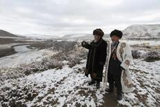 Местные старейшины следят за церемонией закладки первого камня на месте строительства ГЭС в долине реки Нарын 27 октября 2012 года. Гидрогенерирующая госкомпания Русгидро надеется получить от государственного же холдинга Роснефтегаз около $330 миллионов в обмен на долю в капитале для проекта ГЭС в Киргизии, рассказал в интервью Рейтер замглавы компании Джордж Рижинашвили. REUTERS/Vladimir Pirogov