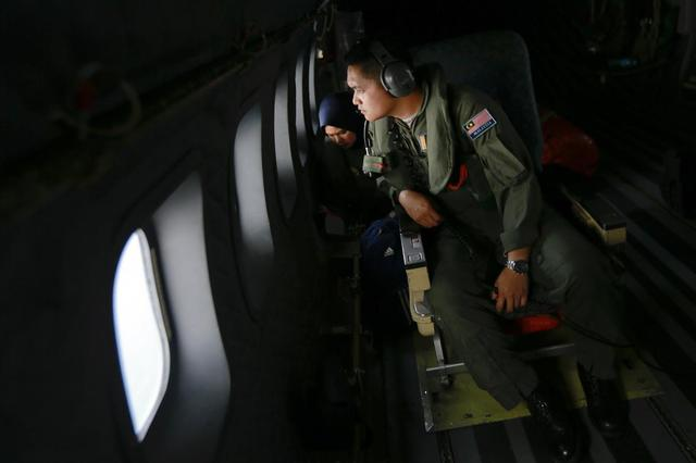 Crew members from the Royal Malaysian Air Force look through windows of a Malaysian Air Force CN235 aircraft during a Search and Rescue (SAR) operation to find the missing Malaysia Airlines flight MH370, in the Straits of Malacca March 13, 2014. REUTERS/Samsul Said