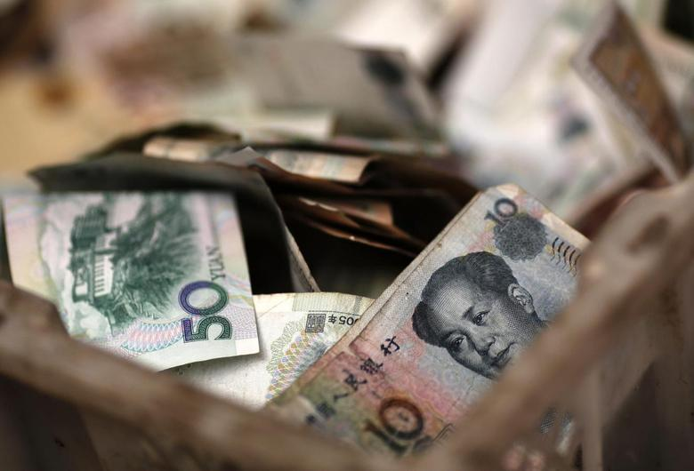 Chinese banknotes are seen at a vendor's cash box at a market in Beijing February 14, 2014. REUTERS/Kim Kyung-Hoon