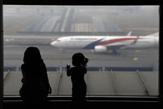 A woman and a girl look at a Malaysia Airlines plane on the tarmac of Kuala Lumpur International Airport March 13, 2014. REUTERS/Damir Sagolj
