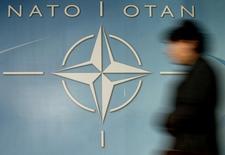 Женщина проходит мимо логотипа НАТО в Брюсселе 4 декабря 2003 года. Россия и Украина приглашены принять участие в заседании 50 стран в штаб-квартире НАТО в пятницу, чтобы обсудить ситуацию на Украине, где пророссийские силы взяли под контроль Крым, сообщили чиновники в четверг. REUTERS/Thierry Roge
