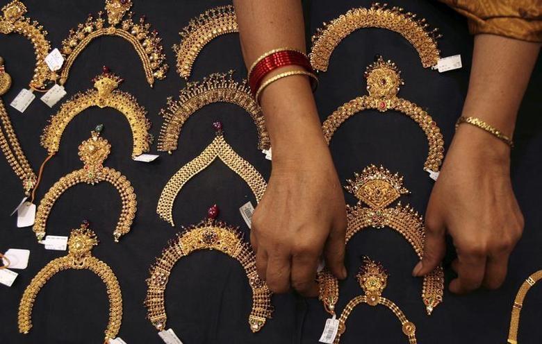 A woman checks a gold necklace inside a jewellery showroom in Hyderabad April 11, 2012. REUTERS/Krishnendu Halder/Files