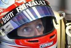 Lotus Formula One driver Romain Grosjean of France looks up during the first practice session of the Australian F1 Grand Prix at the Albert Park circuit in Melbourne March 14, 2014. REUTERS/Brandon Malone