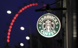 The sign outside a Starbucks coffee shop on in Westminster is seen with the London Eye in the background, in central London, December 3, 2011. REUTERS/Olivia Harris