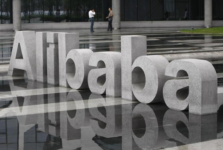 Two men chat beside a logo of Alibaba (China) Technology Co. Ltd at its headquarters on the outskirts of Hangzhou, Zhejiang province May 17, 2010. REUTERS/Steven Shi