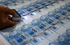 Funcionário verifica folhas de papel-moeda durante uma visita da mídia à Casa da Moeda, no Rio de Janeiro. O Índice de Atividade Econômica do Banco Central (IBC-Br) registrou expansão de 1,26 por cento em janeiro sobre o mês anterior, acima do esperado e indicando que a economia brasileira iniciou 2014 em recuperação, mas ainda insuficiente para compensar a retração vista em dezembro. 23/08/2012 REUTERS/Sergio Moraes
