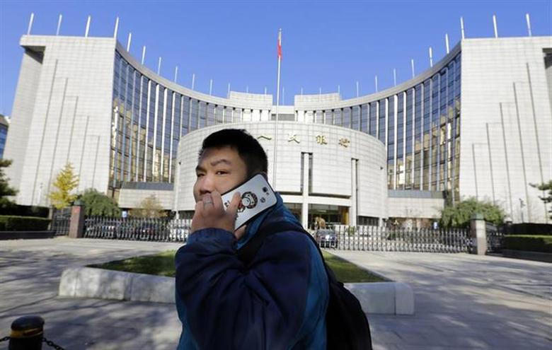 A man uses his mobile phone while walking past the headquarters of the People's Bank of China (PBOC), the central bank, in Beijing, November 20, 2013. REUTERS/Jason Lee/Files