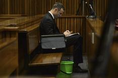 Olympic and Paralympic track star Oscar Pistorius sits beside a green pail in the dock during court proceedings at the North Gauteng High Court in Pretoria March 14, 2014. REUTERS/Phill Magakoe/Pool