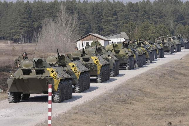 Ukrainian soldiers ride on military armoured personnel carriers as they take part in a military exercise near Kharkiv March 14, 2014. REUTERS/Stringer